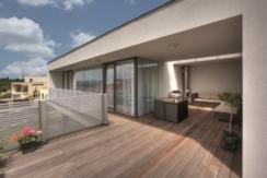 Ansicht von einer großflächigen Terrasse mit einem modernen Balkongeländer aus Aluminium und Querlatten