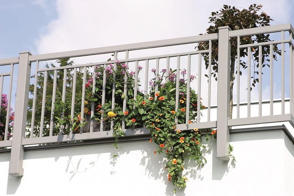 GUARDI Balkongeländer aus Aluminium in grau, dahinter Bäume und Blumen