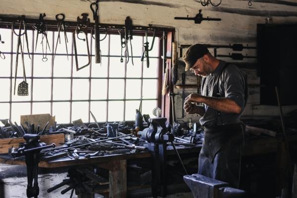 Ein Mann im Arbeitsoutfit steht in einer unordentlichen, gut ausgestatteten Werkstatt