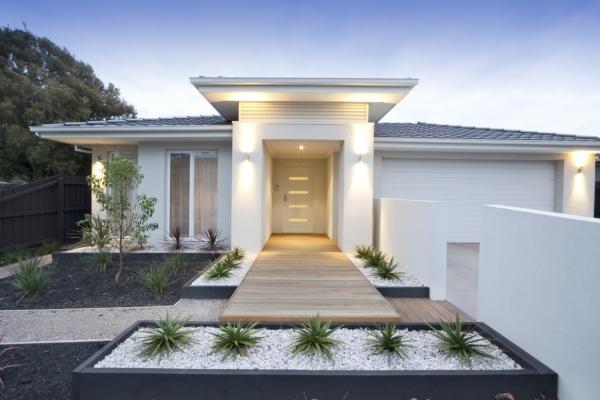 Es wird ein moderner Vorgarten gezeigt, mit einem Eingang zu einem modernen Haus
