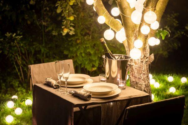 Man erkennt einen beleuchteten Tisch im Garten.