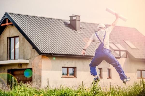 Ein Bauarbeiter springt vor Freude vor einem neuen Einfamilienhaus