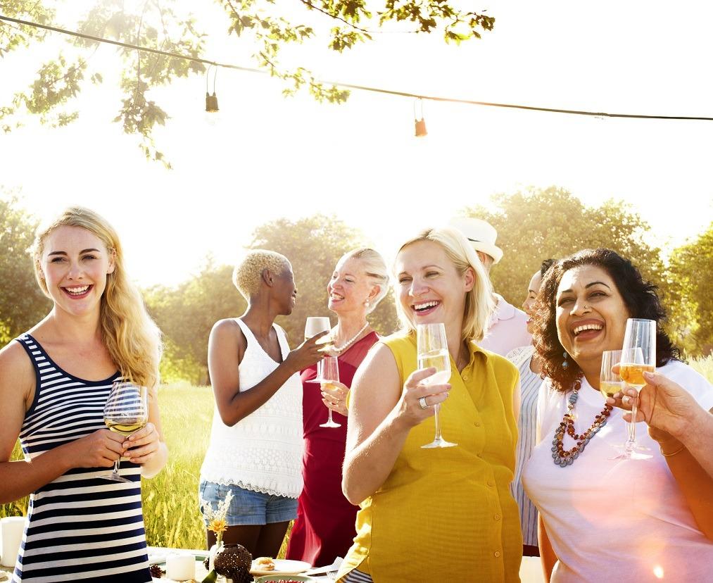 Nachbarn stehen im Garten zusammen und trinken Sekt und Wein