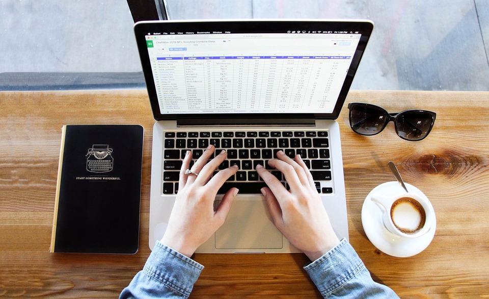 Vogelperpskeitve auf ein Mac Book und Unterlagen zum Arbeiten in einem Cafe