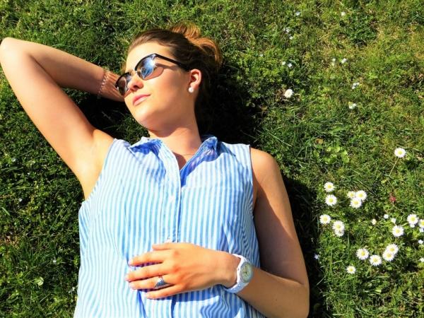Eine junge Frau liegt im Gras und sonnt sich