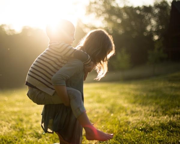 Ein Kind nimmt ein kleineres Kind Huckepack im Freien