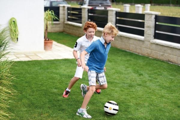 Zwei Jungs beim Fußball spielen auf einem Grundstück, umzäunt durch einen modernen Gartenzaun aus Aluminium