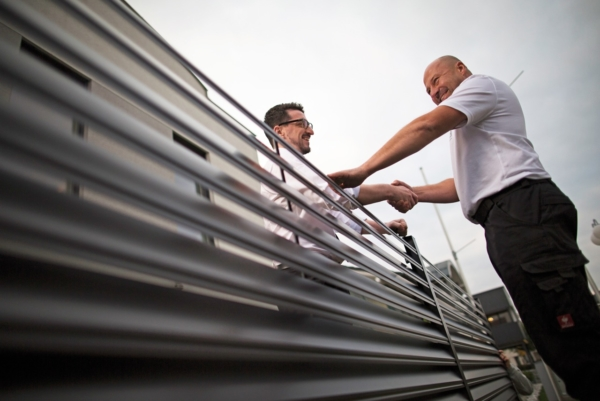 Zwei Männer reichen sich über einen Aluminiumzaun in anthrazit hinweg die Hände