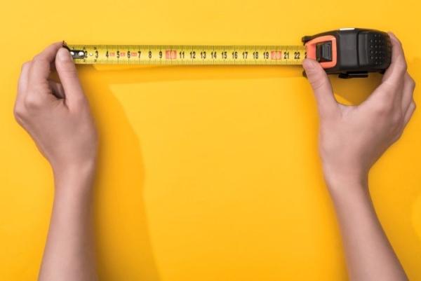 man erkennt männliche Hände, welche ein Maßband halten, Im Hintegrund ist eine gelbe Farbe zu sehen