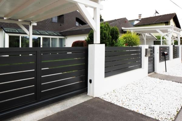 Moderner Sichtschutzzaun mit Querlatten aus Aluminium in anthrazit vor einem Haus