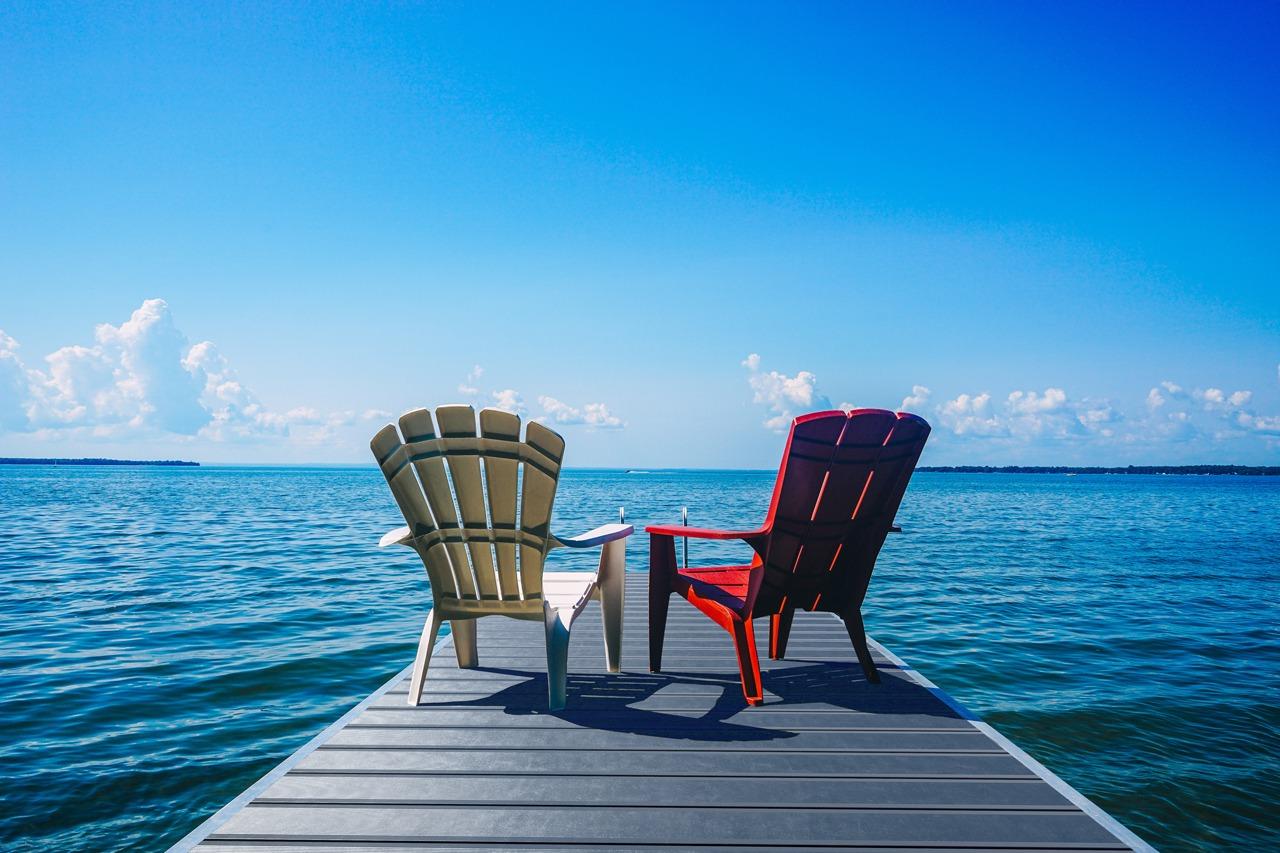 Steg zu einem See ausgelet mit Terrassenprofilen aus Aluminium und zwei Stühlen darauf