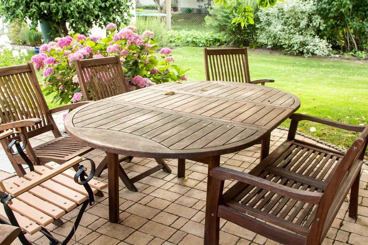 Holztisch mit dazugehörigen Holzsesseln stehen auf der Terrasse, dahinter ist eine Grünfläche zu sehen