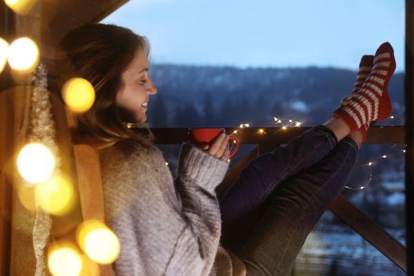 Eine Frau sitzt mit einer roten Tasse am schön weihnachtlich gestalteten Balkon.