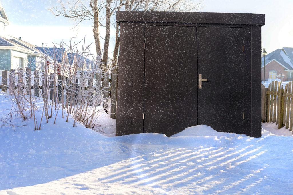 Gartenhütte von GUARDI steht im schneebedecktem Garten, im Hintergrund ein Gartenzaun