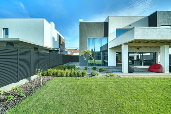 Großes Einfamilienhaus mit Garten, umzäunt von einem Sichtschutzzaun aus Aluminium mit Querlatten in anthrazit