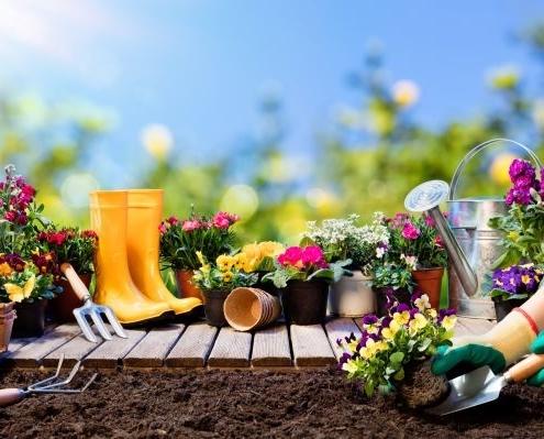 Man erkennt verschiedene Gartenutensilien. Unter anderem Gummistiefel und eine Gießkanne.