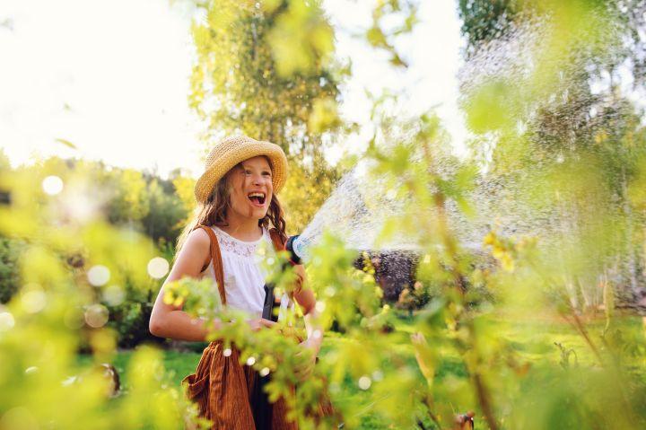Man sieht ein lachendes Kind, das gerade den Garten bewässert