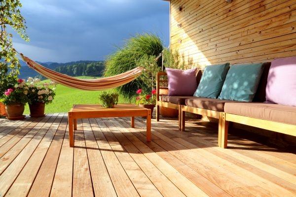 Eine Terrasse mit Terrassendielen aus Aluminium, einer Hängematte und einer Gartenlounge