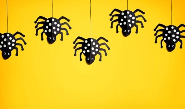 schwarze selbst gebastelte Spinnen hängen auf einem Seil auf gelben hintergrund