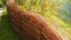 ein Gartenzaun gefüllt mit Totholz