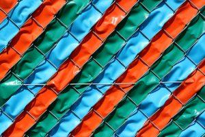 Kunststoffbäner in einem Maschendrahtzaun geflochten in den Farben grün blau und orange