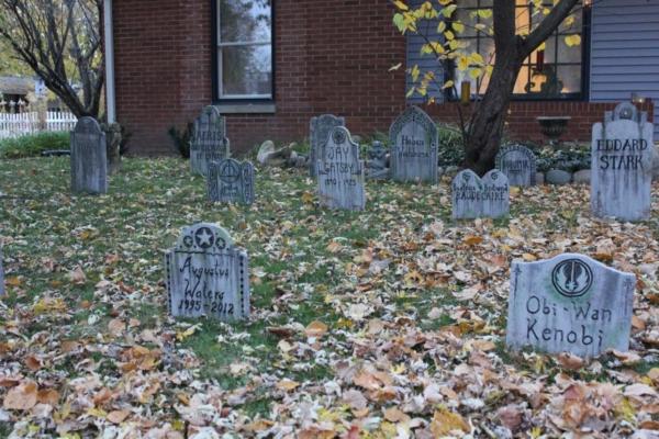 viele Grabsteine stehen auf einer Wiese die bedeckt mit braunen Herbstblatt ist