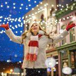 Eine Frau steht im Schneefall und freut sich