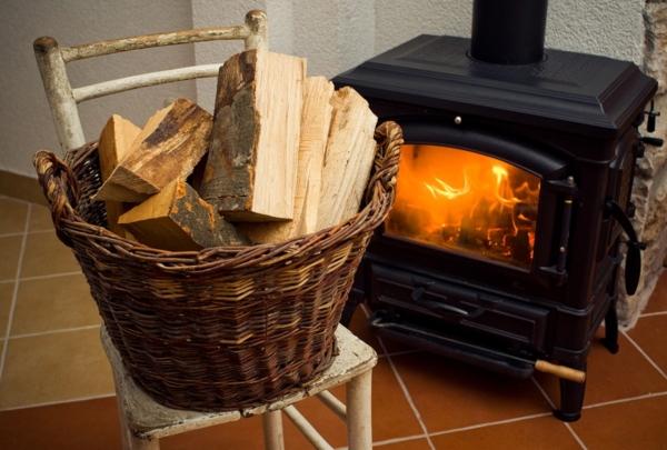 Ein brennender Ofen in einem Wohnzimmer mit Brennholz davor in einem Korb gelagert