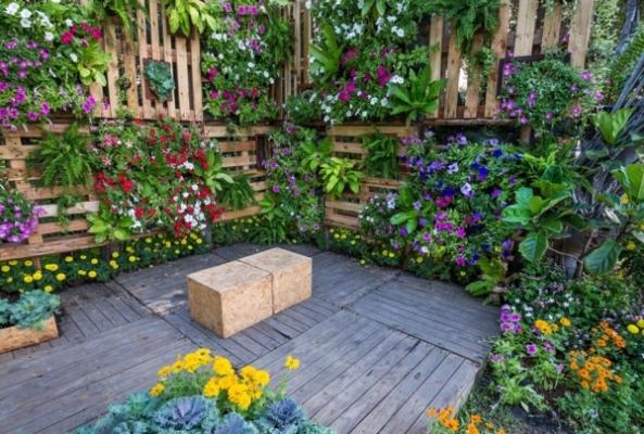 Bild, das Paletten als Mittel zeigt, um vertical gardening zu praktizieren mit vielen Blumen in den Paletten