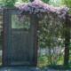 Bild einer Gartentür und eines Gitterzauns, der mit Pflanzen vollgewachsen ist