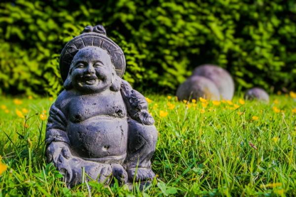 Eine kleine lachende Buddha-Statue steht in einem Garten im Gras