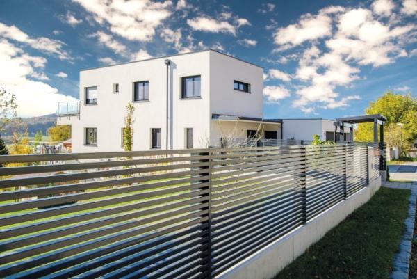Modernes Einfamilienhaus umzäunt mit einem Gartenzaun aus Aluminium mit Querlatten in anthrazit
