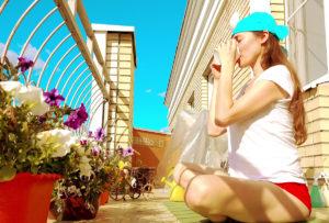 Eine Frau trinkt im Schneidersitz Tee am Balkon, sie absolviert gerade eine Yoga-Session