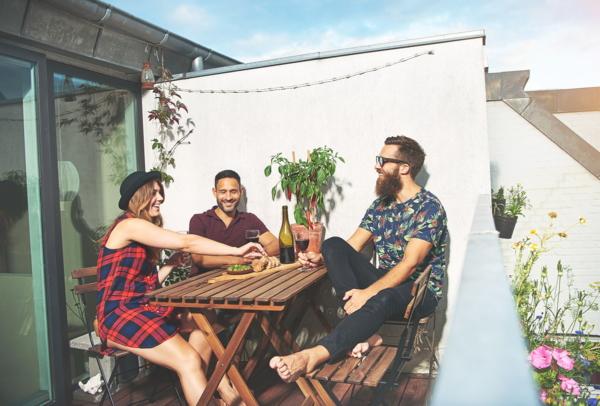 Eine Gruppe junger Menschen sitzt am Balkon an einem Tisch und lacht