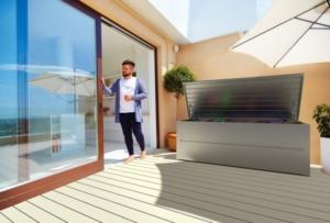 Ein Mann steht auf seiner Terrasse in der Türe, am Balkon steht eine Gartenbox aus Stahl in silber