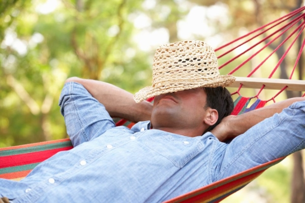 Ein Mann liegt in einer Hängematte und schläft, einen Strohhut hat er übers Gesicht gelegt