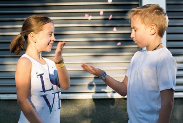 zwei kinder spielen vor einem Sichtschutzzaun