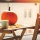 Balkonmöbel aus Holz im Herbstlicht, drauf ein Kürbis und eine Teetasse