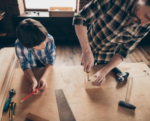 Mann mit einem Kind bastelt in der Werkstatt an einem Holzstück