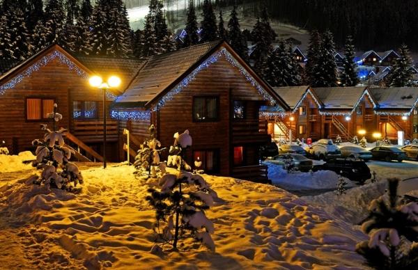 Kleine Siedlung aus Holzhäusern im Winter mit Schnee bedeckt