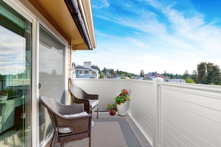 Blickdichter weißer Balkon, am Balkon stehen zwei braune Sessel, im hIntergrund ist eine heller, blaufarbener Himmel zu sehen