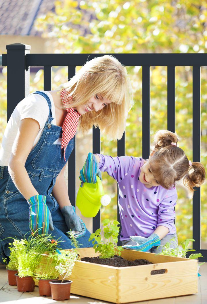 es ist eine Mutter mit Kind zu sehen, beide gießen Pflanzen,, im Hintegrund steht ein schwarzer Zaun