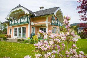 Guardi Modell des Monats Altenmarkt an einem orange gestrichenen Haus, Blumen am Feld vor dem Haus
