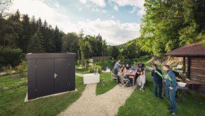 Guardi Gartenhaus in anthrazit steht auf einem Grundstück, dahinter ein Teich mit idyllischem Ambiente, daneben feiern Menschen