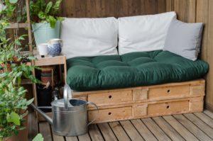 Selbstgemachte Balkonmöbel aus Holzpalletten mit Laden, bedeckt mit Kissen, daneben steht eine Gießkanne und viele Pflanzen