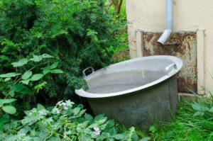 stahltonne im Garten, Regenwasser fließt von der Regenrinne in die Tonne