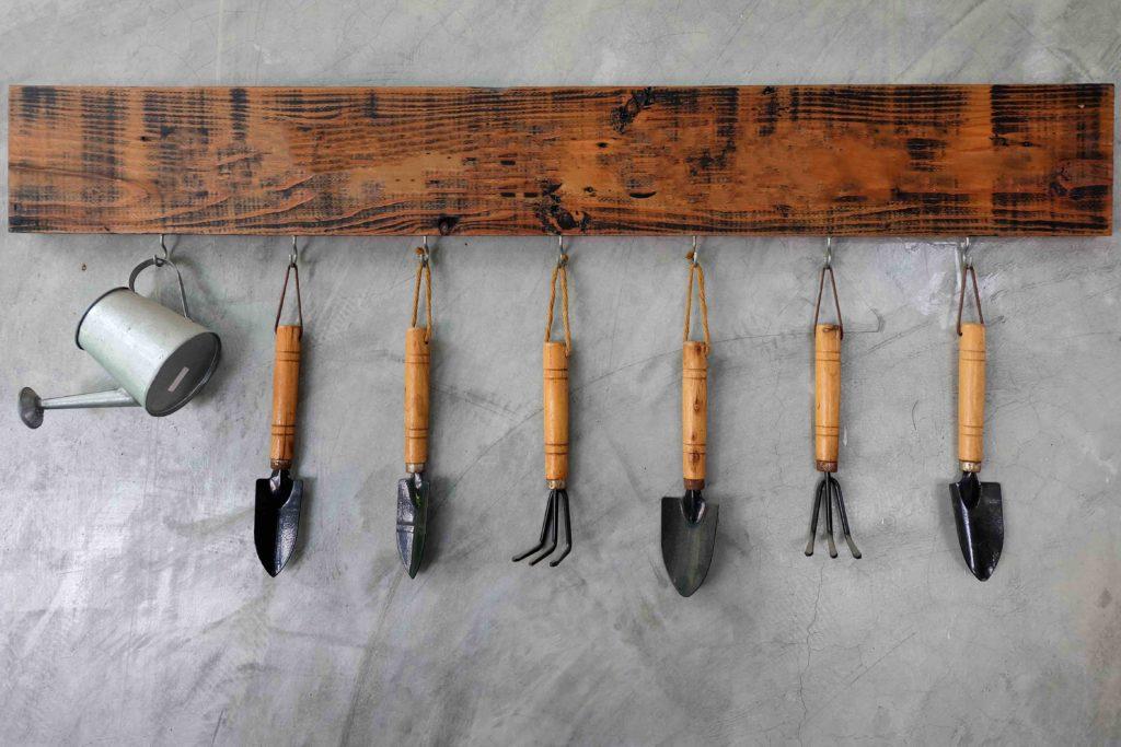 Verschiedenste Gartenwerkzeuge hängen geordnet an grauer Wand