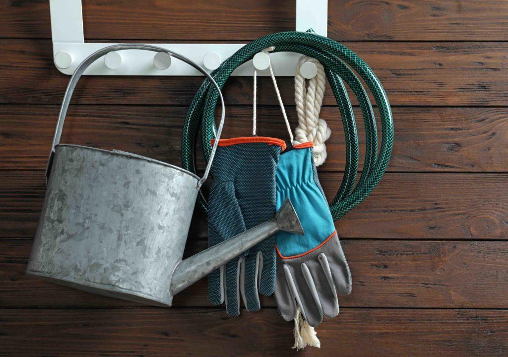 Gießkanne, Gartenhandschuhe und Gartenschlauch hängen an Wand aus Holz