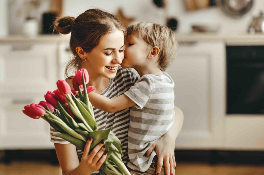 Sohn umarmt Mutter und gibt ihr einen Kuss auf die Wange, sie hält rote Tulpen in der Hand