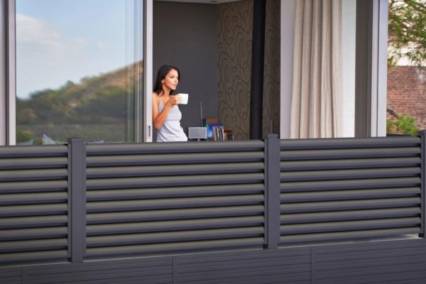 Frau steht mit einer Tasse Kaffee auf dem Balkon, der mit einem modernen Sichtschutzgeländer aus Aluminium von GUARDI umrahmt ist